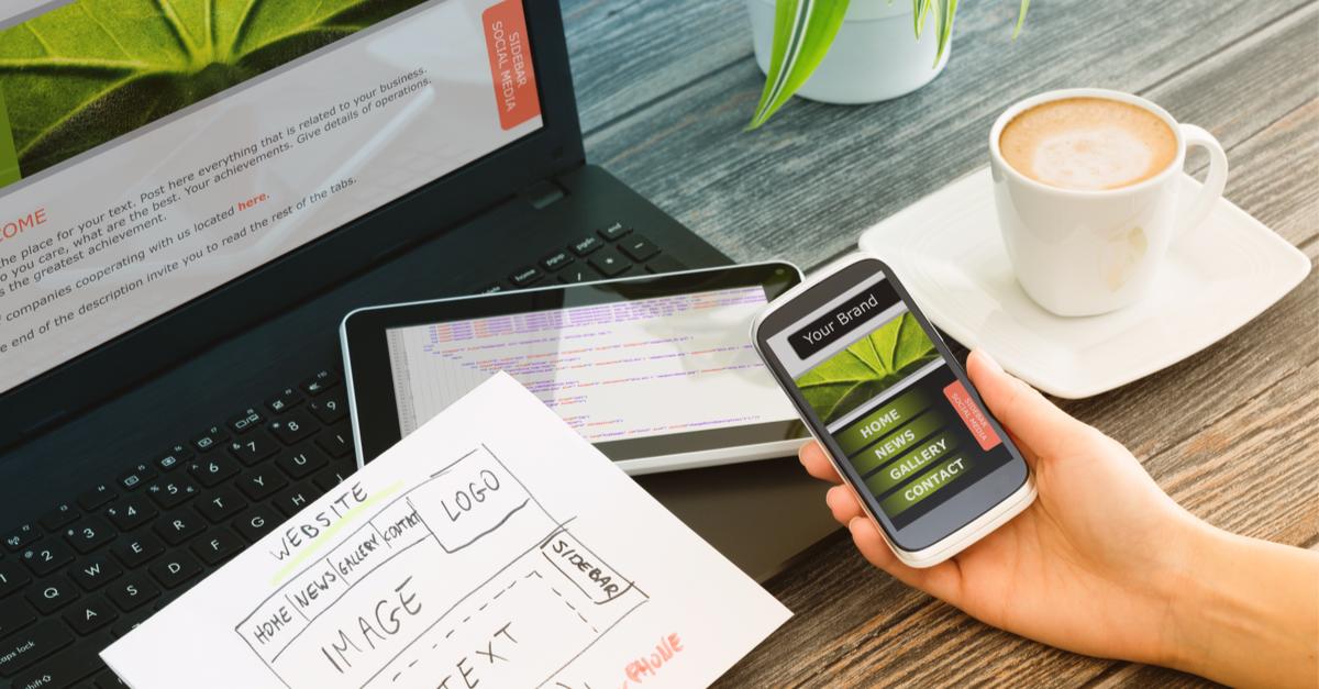 Website designer looks at desktop and mobile versions